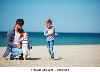 father and sons having fun, running on the sandy beach