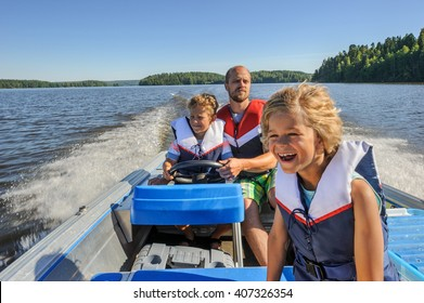 Father and sons out boating together. The father lets one of the boys steer the boat. They're wearing life vests. In the background there's forested shore line, water, and blue sky.