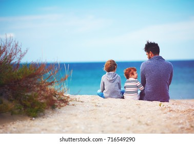 father and sons at sandy beach near the sea on windy day