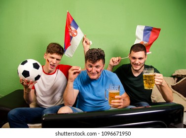 Father and sons , Serbian soccer fans watching game on television