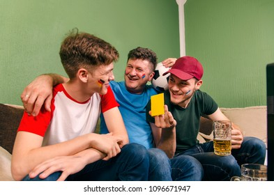Father and sons soccer fans, gathered in front of TV, older brother having fun with younger brother