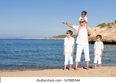 father and sons walking on beach, outdoor