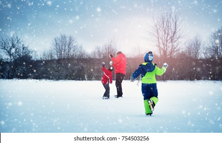 Father with sons walking at snowfall. Children in winter clothes playing with snow and sledding with dad