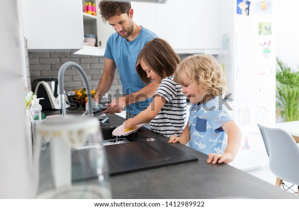 Father and sons washing dishes together