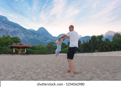 A father is spinning his son around him, taking him by the arms on the beach against the backdrop of a mountain landscape. The concept of a happy family, outdoor activities, positive emotions and