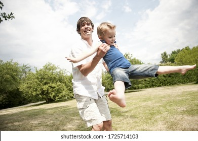 father spinning son around in park