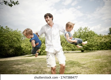 father spinning son's around in park