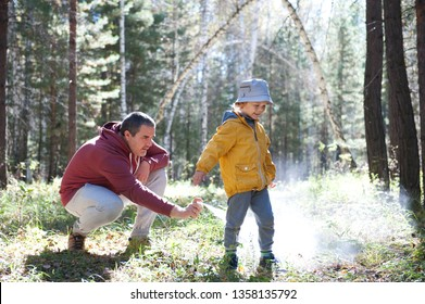 Father spraying insect repellents on his son before a walk in the forest