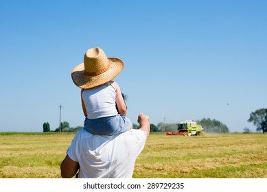 Father standing on field riding son on shoulders pointing at harvester -thresher on summer sunny day over blue sky background copyspace