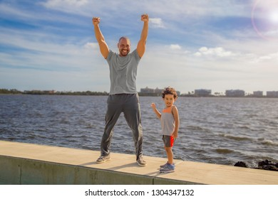 A father stands tall on the sea wall along with his son with both hands stretched high to show the child victory for exercising together. The young boy stands with dad on a seawall at the intercostal.