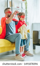 father in superhero costume putting red mask on son while sitting on sofa at home