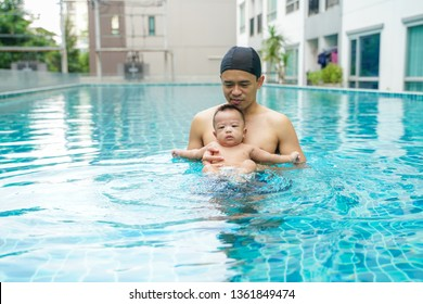 Father swimming with adorable little baby boy  in swimming pool