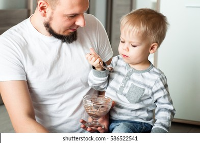Father takes care of his little two years old son, keeping him on the knees. Boy eats ice cream.