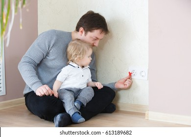 Father takes care of the safety of the child. Electrical security for safety home of ac power outlet for babies, baby hands playing with electric plug