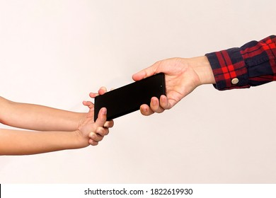 The father takes the phone from his daughter. Children's addiction to mobile games. A thief stole a child's phone. Smartphone in arms close-up. Passing a gift from hand to hand.