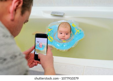 Father takes a photo of his cute child swimming with inflatable ring in the bath tub. Bath time interactions. Family memories