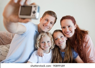 Father taking a family picture on the sofa