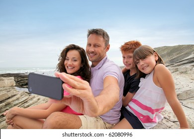 Father taking picture of the family in front of the sea