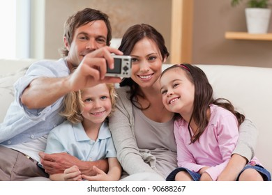 Father taking a picture of his family in the living room