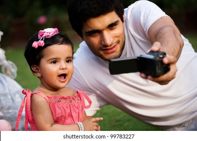 father taking a self portrait with his daughter on digital camera, biracial family