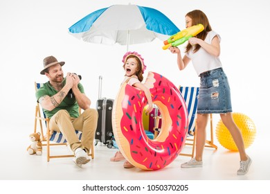 Father taking shot on camera while mother aiming water gun on daughter with flotation ring isolated on white
