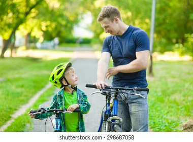 father talking with his son riding a bicycle