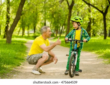 Father talking with his son riding a bicycle and showing thumbs up