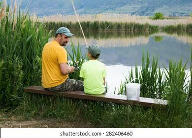 Father talks to son. Fishing on Bountiful Pond (Lake), Utah, US