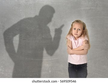 father or teacher shadow screaming angry reproving misbehavior to young sweet little schoolgirl or daughter with beautiful blonde hair sad intimidated looking scared and guilty isolated