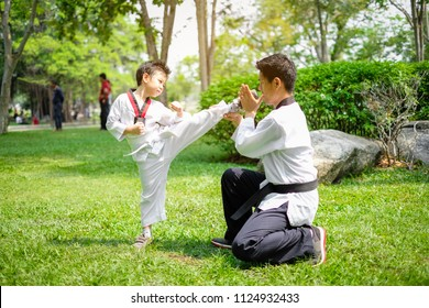 Father is Teacher teaching taekwondo kids, children boy are learning taekwondo in the nature park