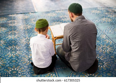The father teaches the child to read the Quran