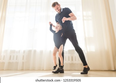 Father teaches to dance his cute little daughter.