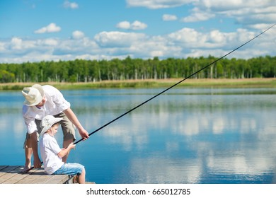 The father teaches his son, to fish on the river from the pier