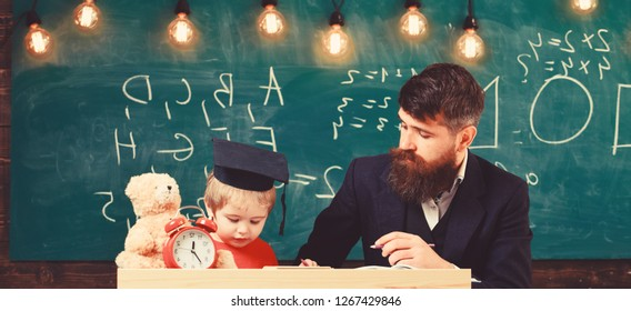 Father teaches son mathematics. Enthusiastic kid studying with teacher. Mathematics lesson concept. Teacher in formal wear and pupil in mortarboard in classroom, chalkboard on background.