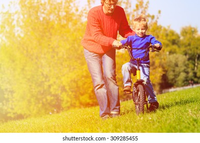 father teaches son to ride bicycle outdoors, kids sport