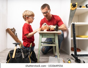 Father teaches son to work with a hand drill.