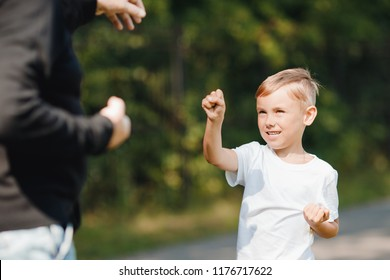 Father teaches young child of boy son to self-defense techniques. Concept hooligans school.