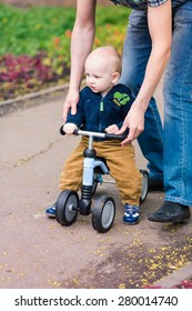 Father teaching baby boy how to ride on his first running bike