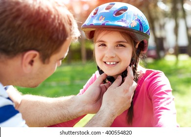 Father teaching brave daughter to ride bicycle putting on safety helmet
