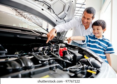 Father teaching car mechanics to his son and pointing the engine