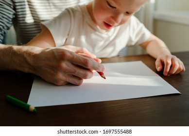 Father teaching child to write or draw with his hands. Red pencil and paper on wooden table. Homeschooling