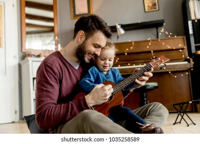 Father teaching daughter to play guitar in the room at home