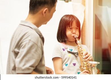 Father teaching daughter to play saxophone. Dad train Asian kid girl blow sax music instrument.Asia Teacher with musical student learn plying jazz music. Jazz Appreciation Month in April.