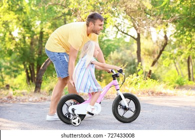 Father teaching daughter to ride bicycle in park on sunny day