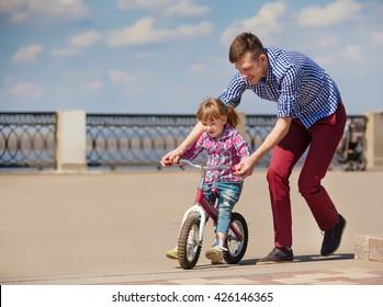 Father Teaching Daughter To Ride Bike