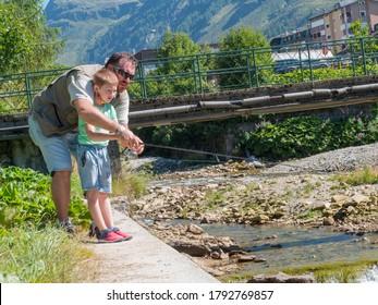 ein Vater lehrt seinen kleinen Jungen am Fluss auf dem Berg zu fischen