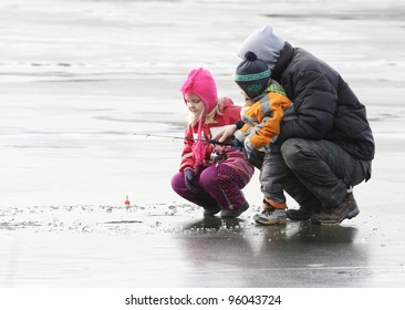 A father teaching his children how to fish on a frozen lake in winter.