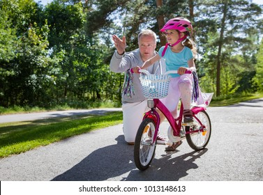Father teaching his daughter to ride bicycle. Happy kid learning riding bike. Family spending time together. Sunny summer day on suburb street.