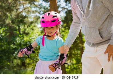 Father teaching his daughter to skate on roller skates. Happy kid in helmet learning skating. Family spending time together. Sunny summer day on suburb street.