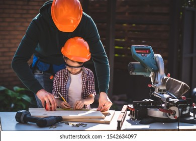 The father teaching his little son to use tools